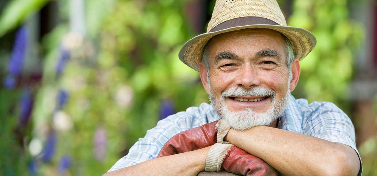 Elderly man working in a garden.
