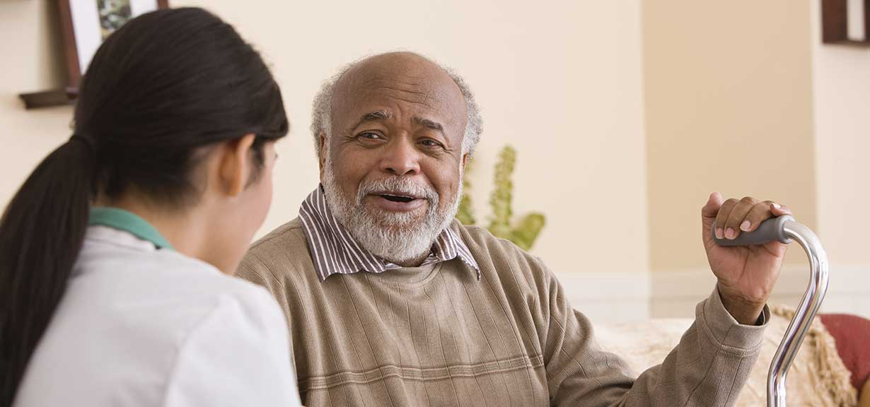 Elderly man talking with a care provider.